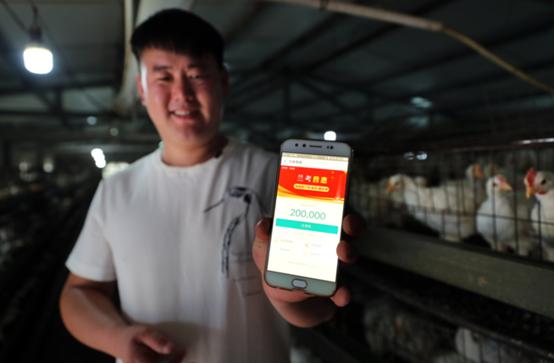 """河南省兰考县南马庄村29岁农民彭家伟在自家鸡棚前,介绍自己从支付宝上贷到了2.4万元,""""瞬间到账""""。"""